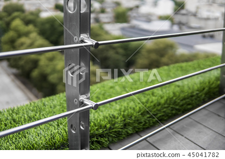 Details of fence made of stainless steel profile with an artificial raffa on the background. 45041782