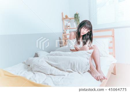 甜美可愛亞洲女孩坐在床上痛苦難過抱著肚子不舒服生病 45064775