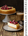 Piece of classic cheesecake with raspberries and coffee on a wooden background. Copy space. 45065831