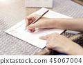 Woman writing plan on notebook, planning agenda 45067004