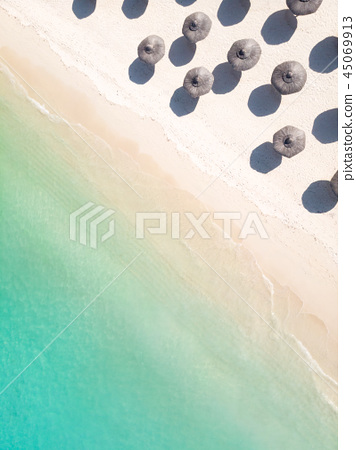 Aerial view of amazing tropical white sandy beach with palm leaves umbrellas and turquoise sea. 45069913