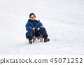 Bearded man sleighing down hill 45071252