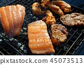 Salmon stake frying outside on the fire 45073513