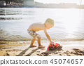 Caucasian child boy plays toy red tractor, excavator on sandy beach by the river in shorts at sunset 45074657