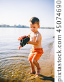 Caucasian child boy playing toy red tractor, excavator on a sandy beach by the river in red shorts 45074690