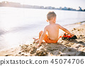 Caucasian child boy playing toy red tractor, excavator on a sandy beach by the river in red shorts 45074706