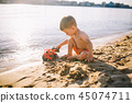 Caucasian child boy playing toy red tractor, excavator on a sandy beach by the river in red shorts 45074711
