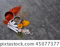 Various spices in measuring cups. 45077377