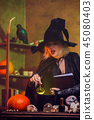 Picture of witch in black hat with book of spells at table with pot, pumpkin 45080403
