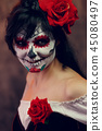 Photo of halloween girl with white makeup on her face 45080497