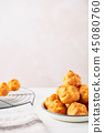 Cream puff cakes on white marble table 45080760