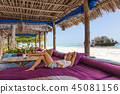 Relaxed woman in luxury tropical bar lounger, enjoying summer vacations on beautiful beach. 45081156