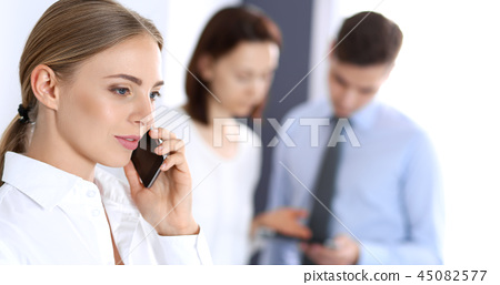 Serious blonde businesswoman talking by phone at the background of her colleagues in office 45082577