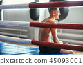 Athletic man rests in ring and laughs 45093001