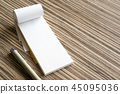 Blank writing pad and pen on wooden background 45095036
