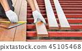 Worker installing wood floor for patio 45105468