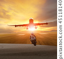 man riding motorcycle on road and plane flying  45118140
