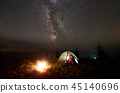 Young couple hikers resting near illuminated tent, camping in mountains at night under starry sky 45140696