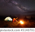 Young couple hikers resting near illuminated tent, camping in mountains at night under starry sky 45140701