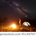 Young female tourist standing near illuminated tent, camping in mountains at night under starry sky 45140707