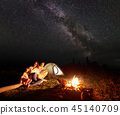 Tourist family with daughter having a rest in mountains at night under starry sky with Milky way 45140709