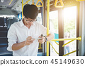 Young Asian man traveler standing on a bus using smartphone watc 45149630