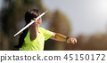 Female athlete throwing a javelin, rear view 45150172