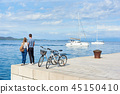 Tourist pair, man and woman with bicycles on high paved stone sidewalk near sea water on sunny day 45150410