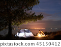 Young couple man and woman having rest at tourist tent and burning campfire on sea shore near forest 45150412