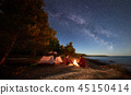 Young couple man and woman having rest at tourist tent and burning campfire on sea shore near forest 45150414