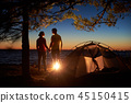 Young couple man and woman having rest at tourist tent and burning campfire on sea shore near forest 45150415