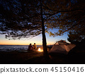Young couple man and woman having rest at tourist tent and burning campfire on sea shore near forest 45150416