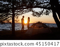 Young couple man and woman having rest at tourist tent and burning campfire on sea shore near forest 45150417