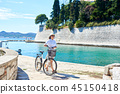 Young woman riding city bicycle near sea 45150418