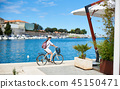 Young woman with backpack riding city bicycle near sea 45150471
