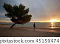 Silhouette of woman alone at water edge, enjoying beautiful seascape at sunset. 45150474