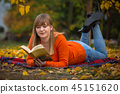 Teenage girl reading a book in autumnal park 45151620