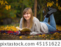 Teenage girl reading a book in autumnal park 45151622