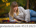 Teenage girl reading a book in autumnal park 45151623