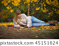 Teenage girl reading a book in autumnal park 45151624