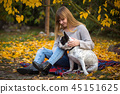 Teenage girl with a dog in autumnal park 45151625