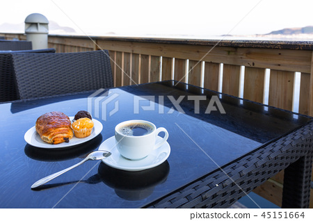 Coffee cup and croissant on the table by the sea 45151664