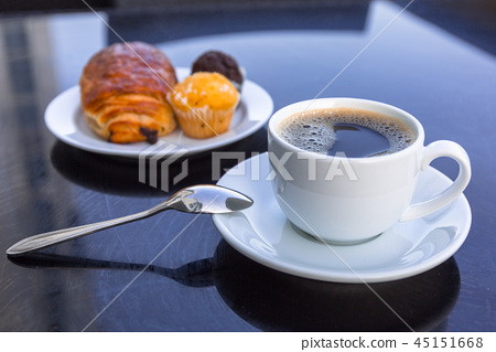 Coffee cup and croissant on the table by the sea 45151668