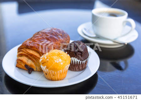 Coffee cup and croissant on the table by the sea 45151671