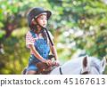 Cute asian child girl riding a horse in the farm 45167613