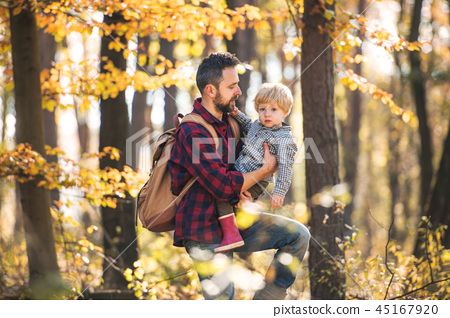 A mature father with a toddler son on a walk in an autumn forest. 45167920