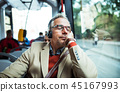 Mature tired businessman with heaphones travelling by bus in city. 45167993