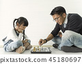Happy asian family playing chess together. 45180697