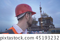 Man in a helmet, architect, engineer, manager tells about the progress of construction in evening 45193232