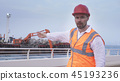 Man in a helmet, architect, engineer, manager tells about course of repair work of the coastline 45193236
